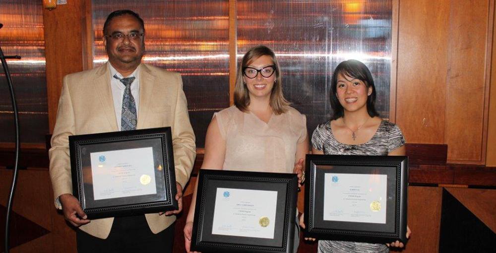 Three graduates hold up framed degrees