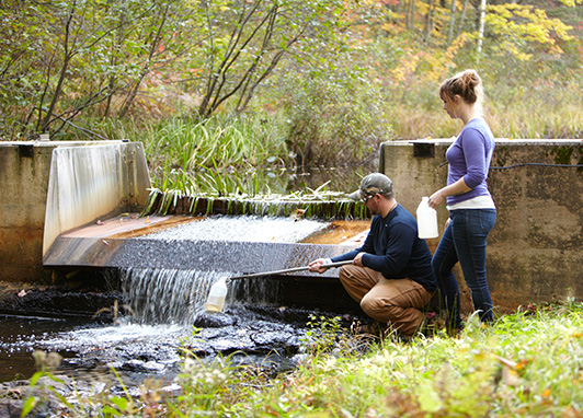 Two people take water samples from a river