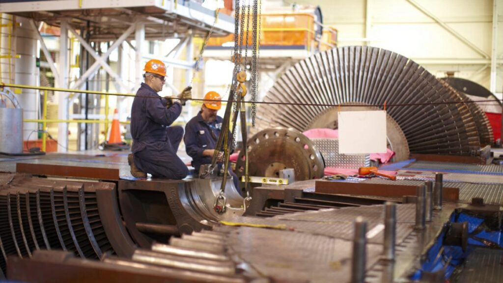 Workers perform maintenance on equipment
