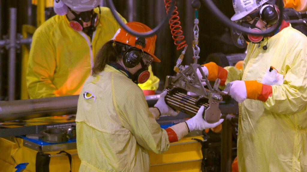 Workers handle fuel bundle