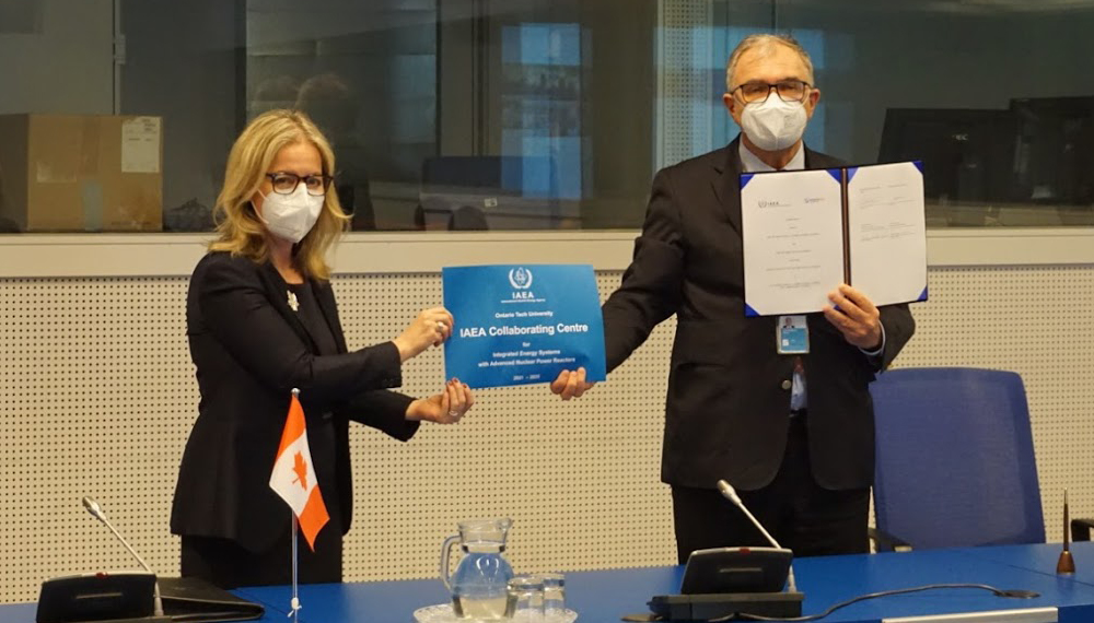 Two masked delegates hold up signed agreement