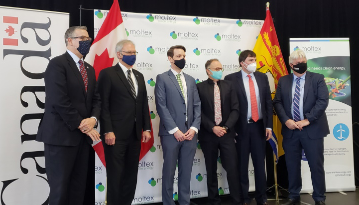 Six people in face masks pose in front of Canada and Moltex banners