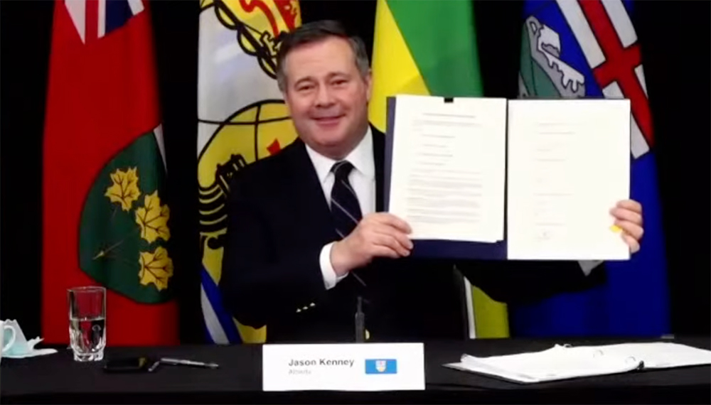 Jason Kenney holding up a signed MOU